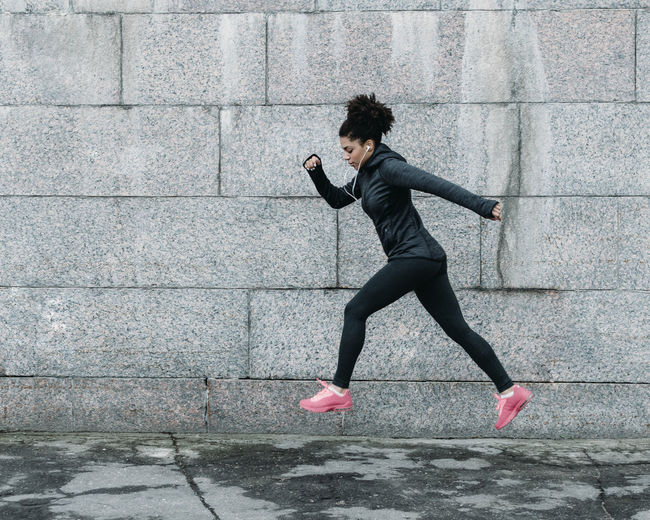 Side View Of Young Woman Jumping While Jogging Against Wall