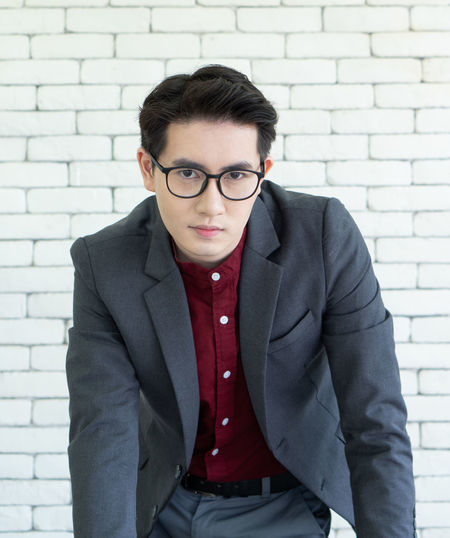 Portrait of young businessman standing against wall