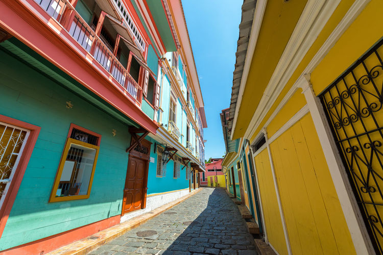 Low angle view of alley amidst multi colored houses on sunny day