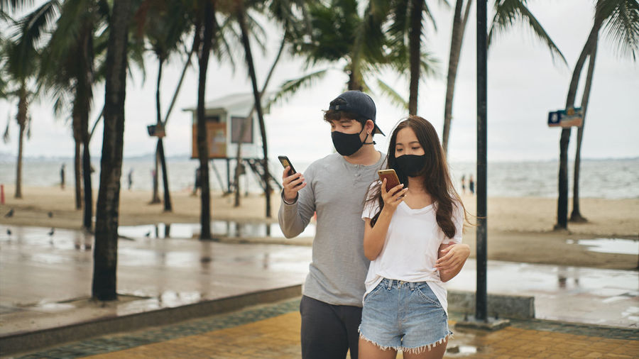 Young man and young woman looking at a smartphone at the beach