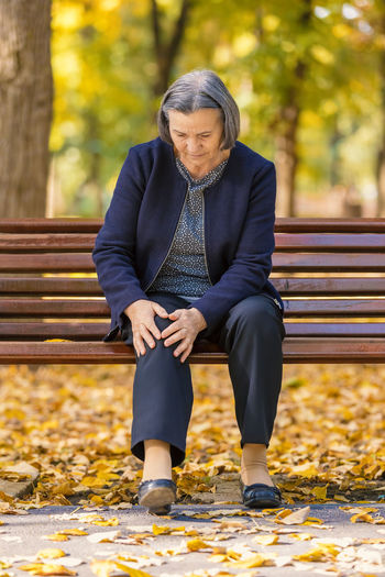 Woman With Knee Pain Sitting On Bench At Park