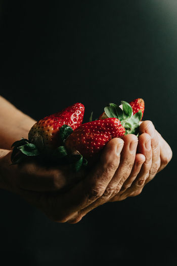 Midsection of person holding strawberry against black background
