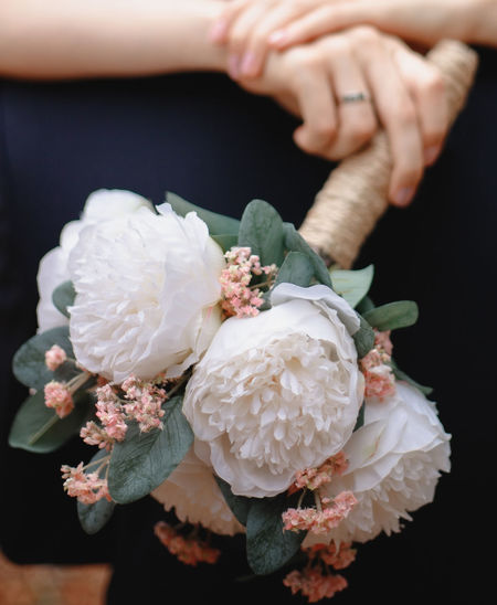 Close-up of hand holding white roses
