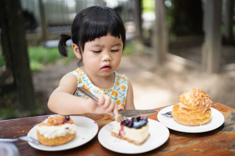 Full length of cute baby girl in plate on table