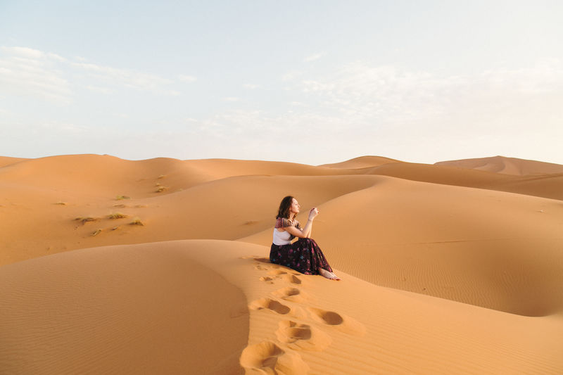 Young woman sitting on sand dune in desert against sky