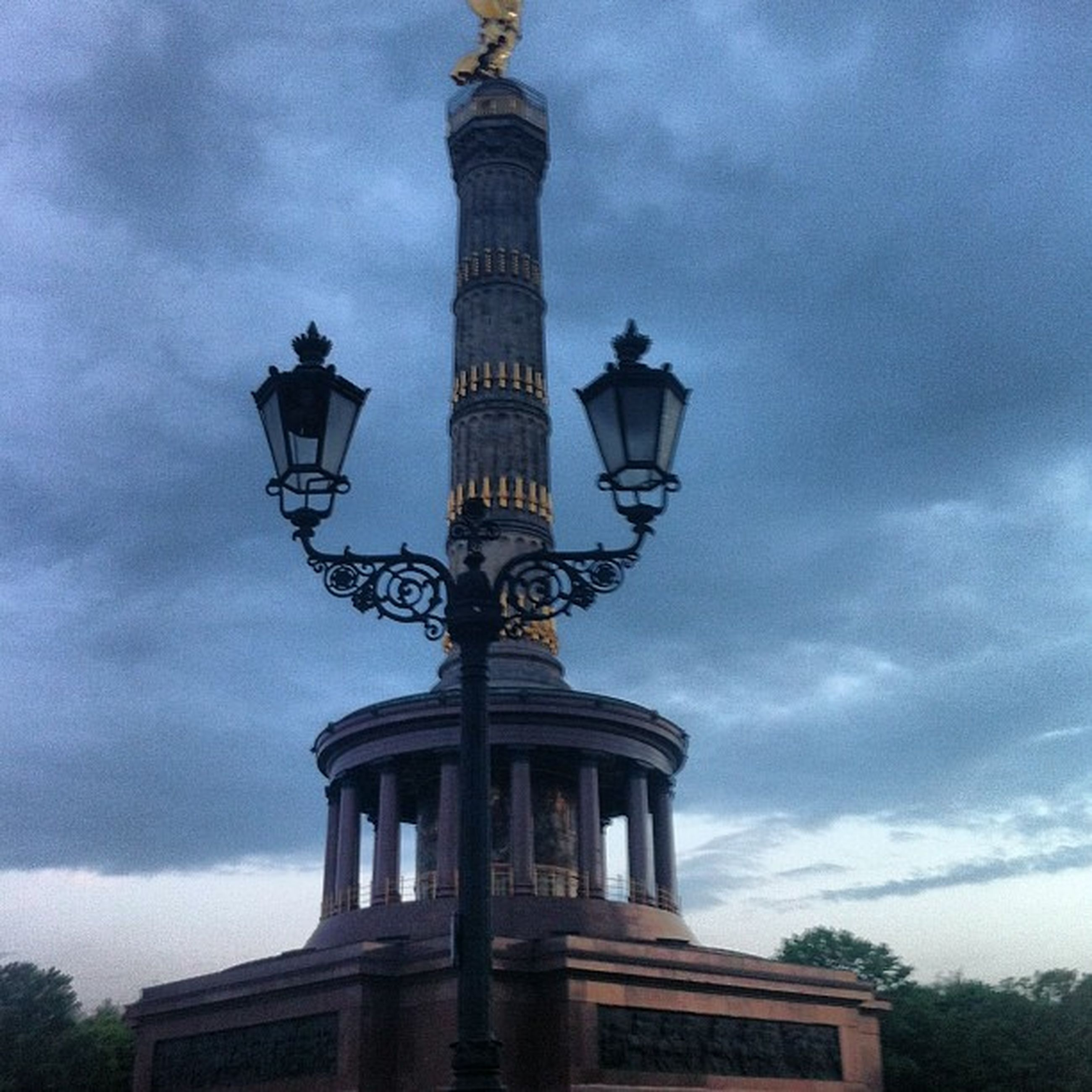 low angle view, sky, built structure, cloud - sky, architecture, building exterior, cloudy, cloud, street light, lighting equipment, high section, no people, outdoors, day, overcast, weather, cross, lamp post, building, dusk