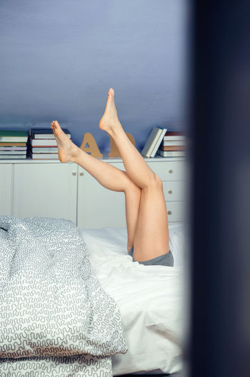 Low Section Of Mid Adult Woman Lying On Bed