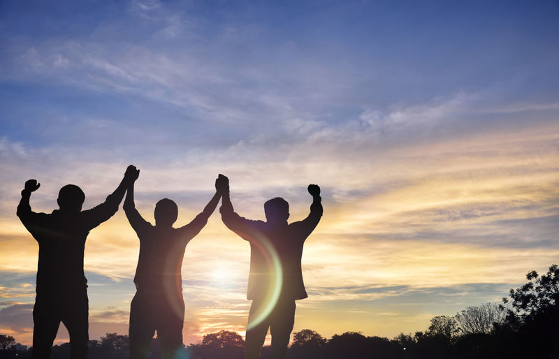 Teams that are willing to share success, stand together, hold hands, look to the sunset the background.Silhouette image Business Agreement Communication Concept Corporate Corporate; Freedom; Happiness; Joy; Meeting; Outdoor