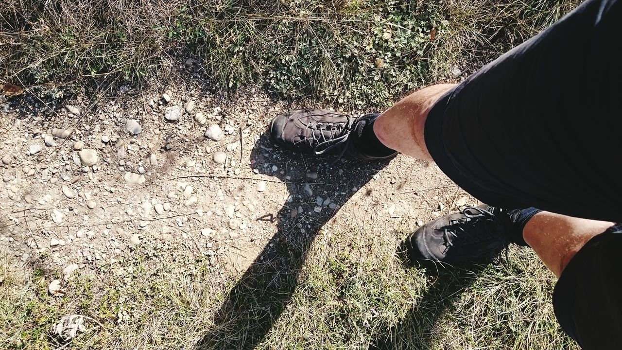 low section, shadow, sunlight, human leg, real people, one person, shoe, high angle view, day, men, lifestyles, outdoors, standing, human body part, grass, one man only, people