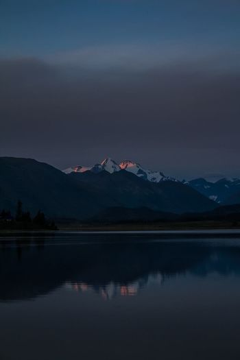 Scenic View Of Lake By Snowcapped Mountains Against Sky At Sunset