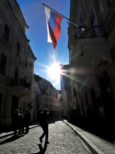 Streetphotography People Photography Tallinn Old Town Flag City Sunlight Sun Flag Politics And Government Lens Flare Sunbeam Sky Architecture Building Exterior