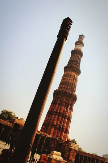 The QutubMinar and the centuries old, non-rusty iron pillar in the foreground. Ironpillar Pillars Delhi EyeEm Best Shots - Architecture Opticalillusion