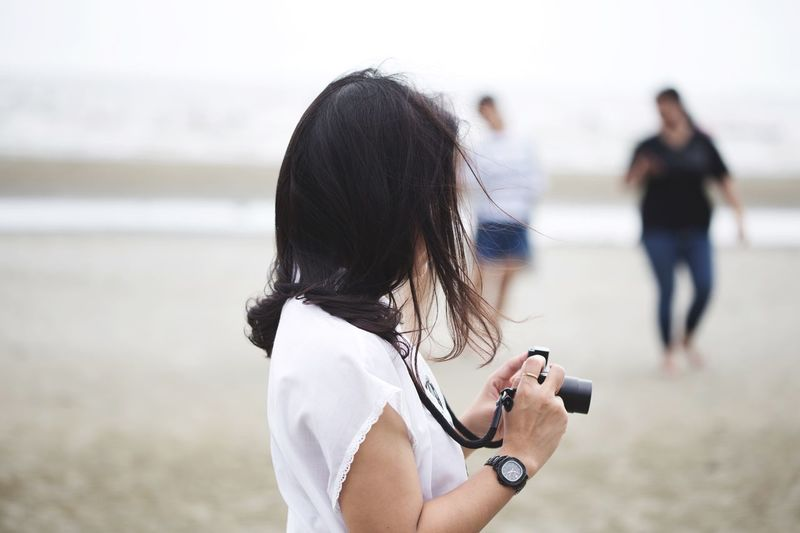 Rear view of woman holding mobile phone at beach