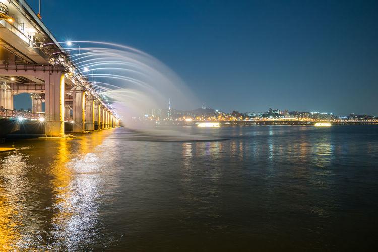 Fountain at banpo bridge over han river against sky at night