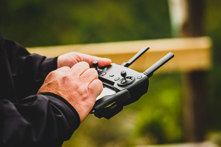 Hand holding drone quadcopter UAV remote control console controls. Professional drone operator is flying a remote control aerial vehicle drone in the nature with green background. Drone  Helicopter Quadcopter Flying Remote Remote Control Uav Uav Drones Gadget Spying Piloting Aerial Vehicle Multicopter Sky Clouds Nature Photographing Surveillance Wireless Technology Controlling Human Hand Controller Pilot Joystick