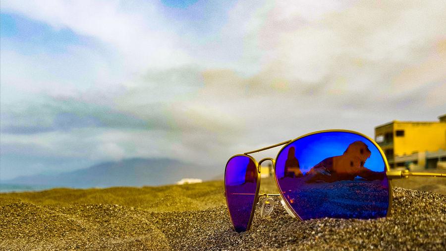 Close-up of sunglasses on beach against sky