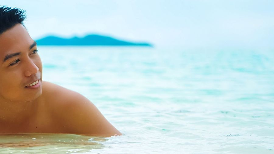Close-up of shirtless young woman against sea