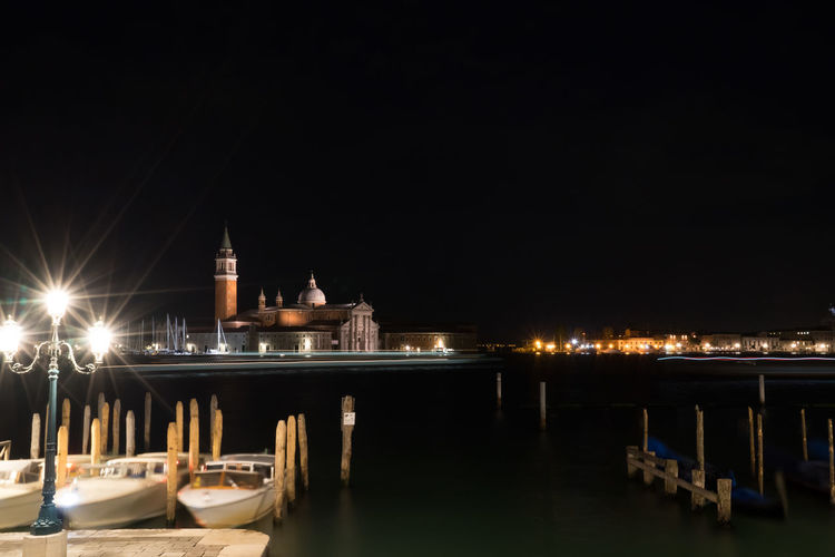 Grand canal by illuminated church of san giorgio maggiore against clear sky at night