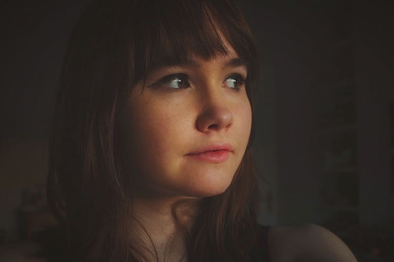 Close-up of thoughtful young woman with bangs