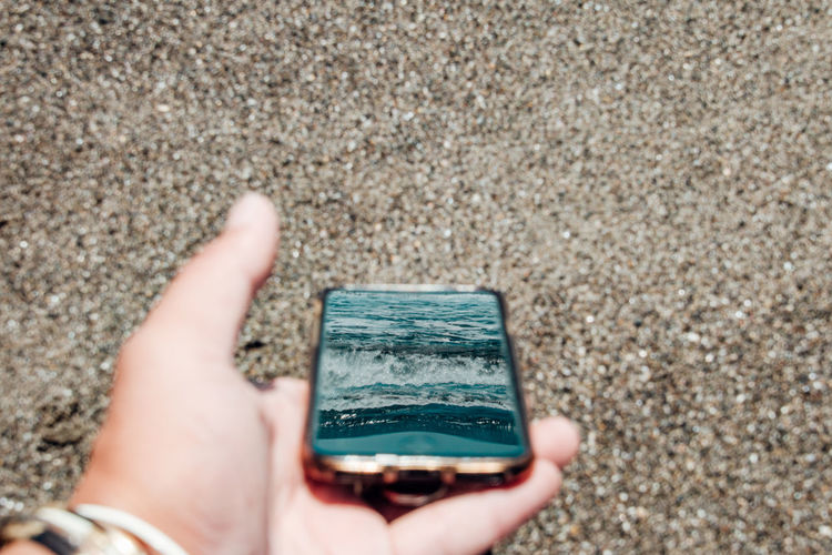 Close-up of hand holding smart phone reflected sea against beach