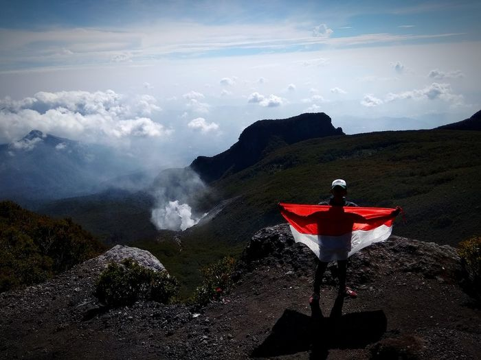Man Holding Flag While Standing On Mountain Against Sky