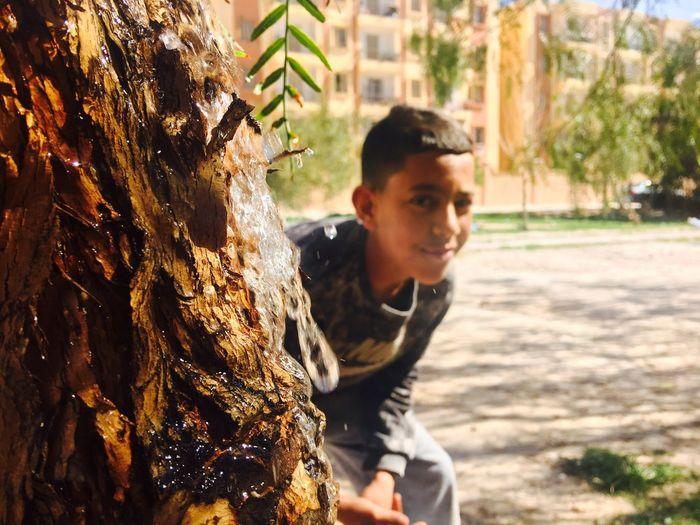 Boy hiding behind wet tree trunk