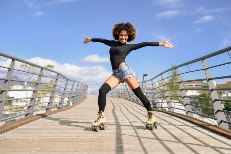 Black woman, afro hairstyle, on roller skates riding outdoors on urban bridge with open arms. Smiling young female rollerblading on sunny day. Beautiful clouds in the sky. Bridge - Man Made Structure Day Energetic Full Length Jumping Leisure Activity Lifestyles Mid-air Motion One Person Outdoors Railing Real People Rollerblading Rollerskating Skates Skating Sky Sports Clothing Sunlight Women Young Adult Young Women