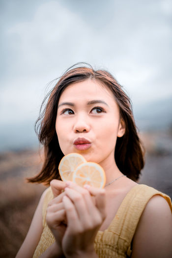 Portrait of young woman holding ice cream at beach against sky