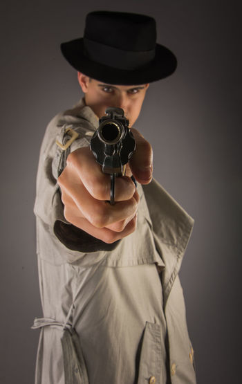 Young man at topcoat with a gun Crime Gangsta Gangsta Style Gun Handgun Hat Lifestyles One Person Real People Silver Background Standing Studio Shot Topcoat Young Men
