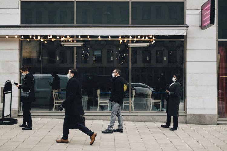 People walking on footpath against building