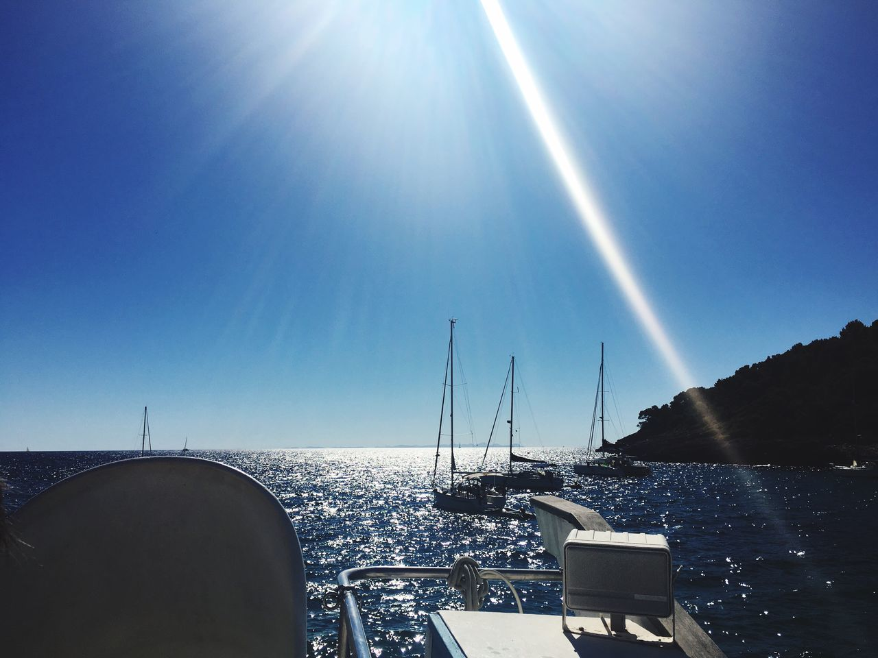 sunlight, sunbeam, water, sea, lens flare, blue, transportation, day, clear sky, nautical vessel, beauty in nature, nature, no people, sun, sky, outdoors, scenics, sailing, horizon over water