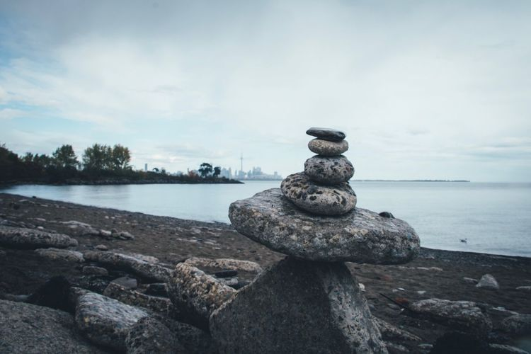 Stack of stones on beach against sky