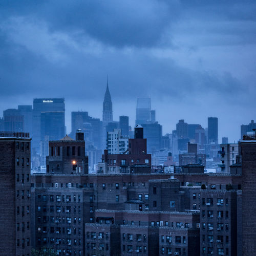 Chrysler building against cloudy sky in city at dusk