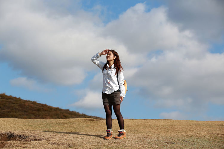 Full length of woman shielding eyes while standing on field against sky
