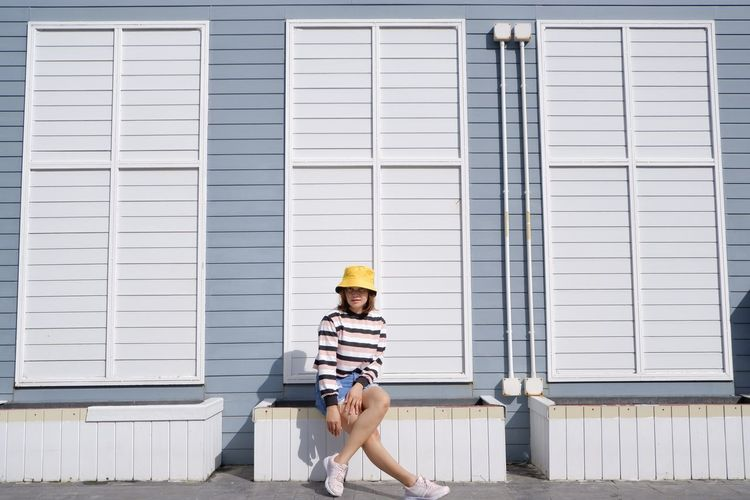 Full length of young woman wearing hat against building