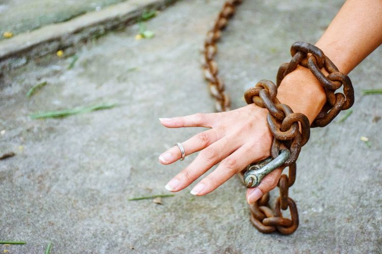 Close-up of hand tied with metal chain