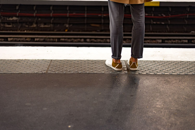 Low Section Of Woman Standing At Railroad Station Platform