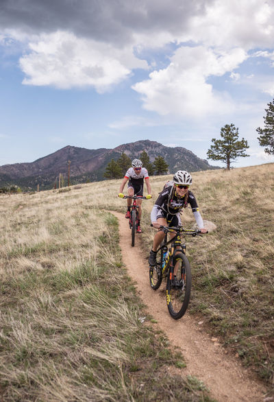 Woman and man mountain biking. Athletic Bicycle Celebrate Your Ride Cycling Day Gear Lifestyle Man And Woman Mountain Biking Mountains Outdoors Recreation  Trail