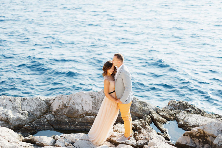 Side view of couple on rock by sea