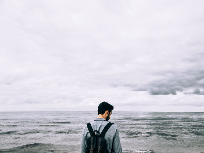 Rear view of teenage boy with backpack standing by sea against cloudy sky