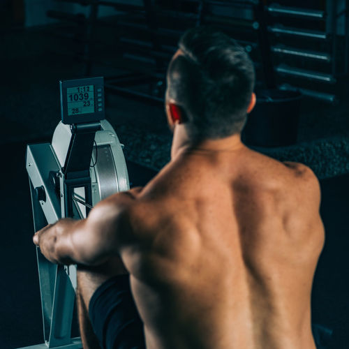 Rear View Of Shirtless Male Athlete Exercising In Gym