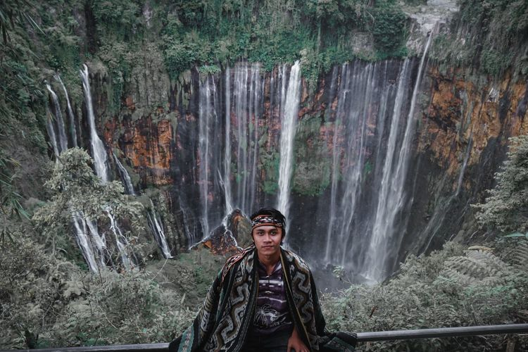 Portrait of man standing on rock against waterfall