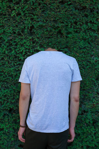 Rear view of man with head in bushes