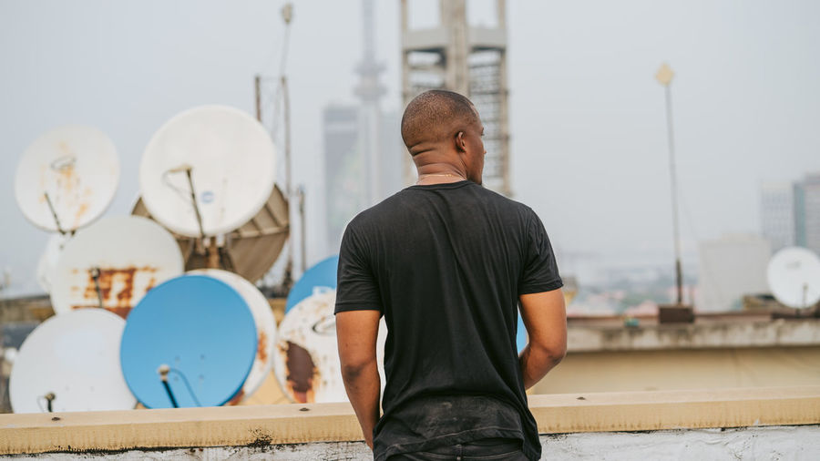Rear view of man standing against wall in city