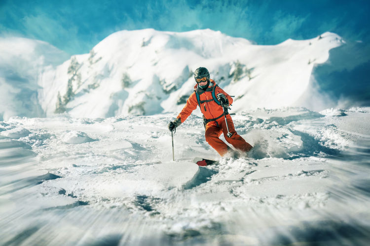 Low Angle View Of Mature Woman Skiing On Snow Covered Mountain