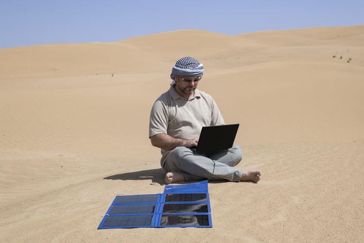 Adult man using his computer charging with flexible solar panels in the middle of the dunes. Going Remote Hot Working Adventure Arid Climate Climate Communication Connected Connection Desert Environment Full Length Land Landscape Laptop Leisure Activity Nature One Person Real People Sand Sand Dune Sitting Technology Using Laptop Wireless Technology Going Remote Going Remote
