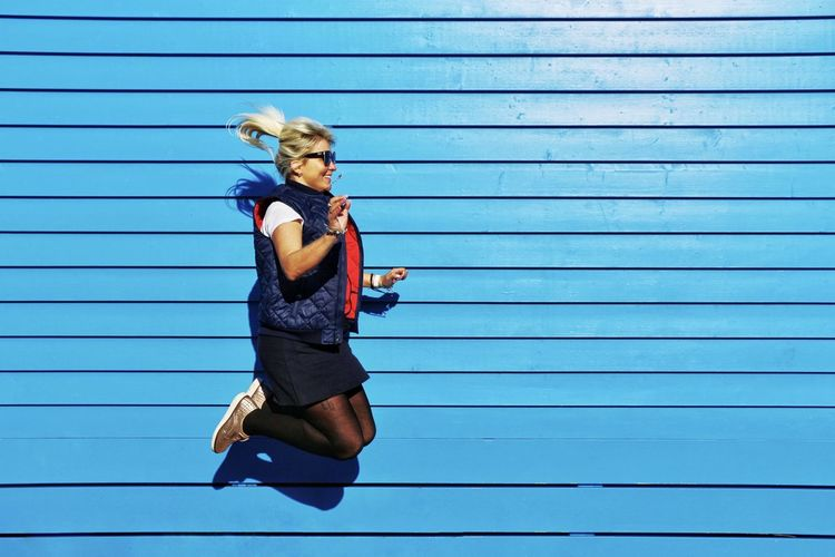 Full length of young woman jumping against blue wall
