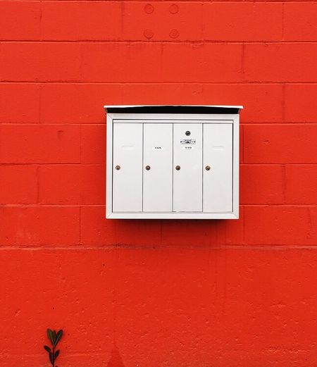 Mailboxes against a bold coloured orange/red wall. Wall - Building Feature Exterior Architecture Mailboxes Bold Colors Red Wall Orange Wall  Concrete Block Concrete Minimalism Simple Background Backgrounds