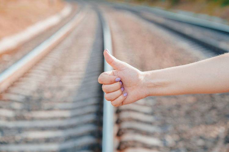 Cropped Hand Holding Showing Thumbs Up Above Railroad Tracks