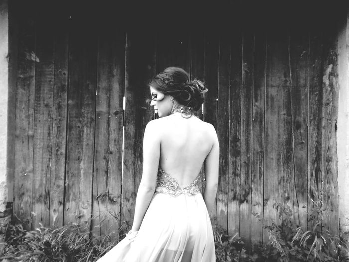 Rear view of young woman wearing backless dress standing by house